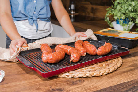 Grilled sausages in a grill pan for baking. Convenience food, precooked.Raw chicken grilled sausages on the table in the hands of the girl. Imagens