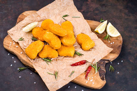 Breaded nuggets on a wooden kitchen board with chili and lemon wedges. Convenience food, precooked.Fast food.various chicken nuggets on wooden cutting board.