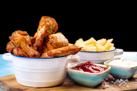 Fried chicken dippers in bucket with sauce on blue background.Chicken breaded strips in small ceramic pots with ketchup and white sauce .Precooked food.Convenience foods.Tender raw chicken