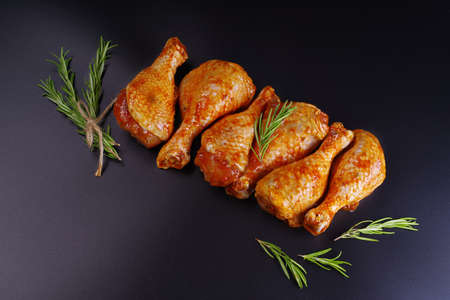 Fresh chicken legs. Raw chicken drumstick with spices and green rosemary on a black background. Raw chicken skewers on skewers. Convenience food, precooked.