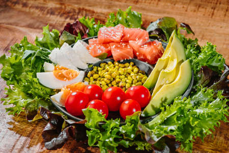 Super food. Healthy food, diet food.Smoked salmon salad poke bowl with avocado, eggs, cucumber and greens and radishes. Imagens