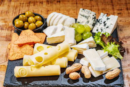 Cheese plate served with grapes, various cheese on a platter. Assorted different types of cheese on a black flat board with olives and nuts. Cheese plate on a wooden table.