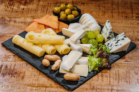 Cheese plate on a wooden table.Cheese plate served with grapes, various cheese on a platter.Assorted different types of cheese on a black flat board with olives and nuts.