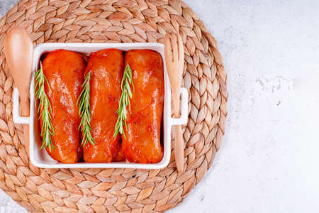 Fresh chicken meat on a light background, copy space. Raw marinated chicken fillet in a baking dish with serving plates. Imagens