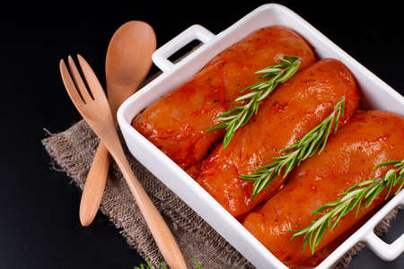 Fresh chicken meat on a light background. Raw marinated chicken fillet in a baking dish with serving plates. Imagens