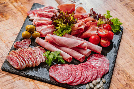 Cold cuts of different types of sausages on a black flat plate on a wooden table with vegetables. Super food.Different types of sausages with sauce served on wooden table.