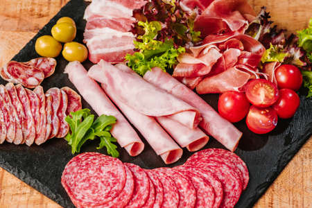 Cold cuts of different types of sausages on a black flat plate on a wooden table with vegetables. Different types of sausages with sauce served on wooden table. Imagens