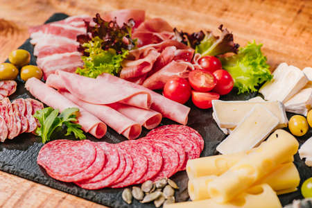 Cold cuts of different types of sausages on a black flat plate on a wooden table with vegetables. Different types of sausages with cheese served on wooden table.