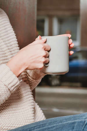 A girl in a beige sweater holds a cup of tea in her hands. Imagens