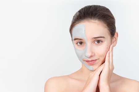Portrait of a young attractive girl with a cosmetic mask on her face. Close-up. Face skin care concept.Beautiful girl with a cosmetic mask made of clay on her face. Cosmetic procedures.