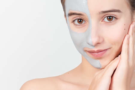 Portrait of a young attractive girl with a cosmetic mask on her face. Face skin care concept.Beautiful girl with a cosmetic mask made of clay on her face. Cosmetic procedures.Close-up.