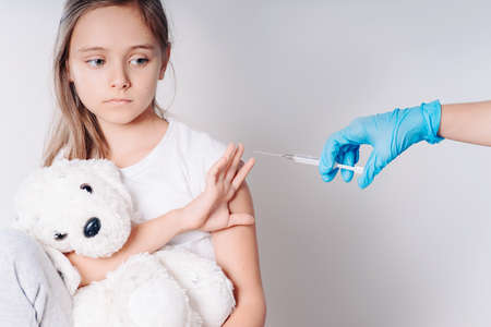 The girl does not want to be vaccinated. Against vaccination. Bad vaccine. Girl holds hand near face protest against vaccine next to doctor's hand with syringe with vaccine, medicine.Angry and distrustful patient refuses to receive it. Imagens