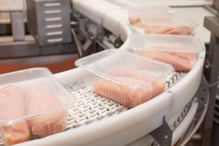 Conveyor Belt Food.Factory for the production of food from meat.Production line with packaging .Food products meat chicken in plastic packaging on the conveyor.