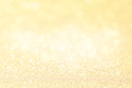 Gold background. Soft focus. Selective focus. Defocus light.Abstract holiday background, beautiful shiny Christmas lights, glowing magic bokeh.