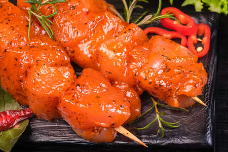 Chicken pieces of kebabs marinated in a red marinade with spices on a dark culinary board, on a background with pieces of pepper. Raw chicken pieces on skewers. Marinated chicken meat.