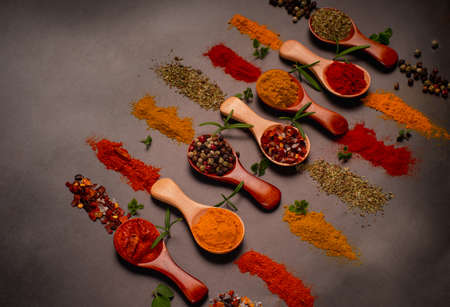 Assorted various spices on wooden spoons on a dark background.