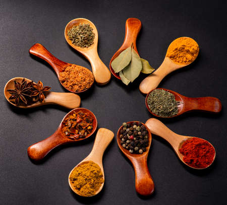 Assorted various spices on spoons on a dark background with laurel leaves.