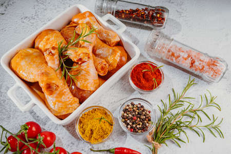 Raw marinated chicken drumsticks sprinkled with spice, chili pepper pieces, bay leaves prepared to cook in a dish, view from above. Drumstick marinated chicken in red marinade with spices. Raw marinated chicken meat. Raw drumstick.