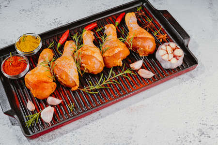dramstick on a grill pan with spices. Raw marinated chicken drumsticks sprinkled with spice, chili pepper pieces, bay leaves prepared to cook in a dish, view from above. Imagens