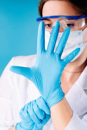 Girl medical worker dresses blue rubber gloves.Hands in protective gloves.