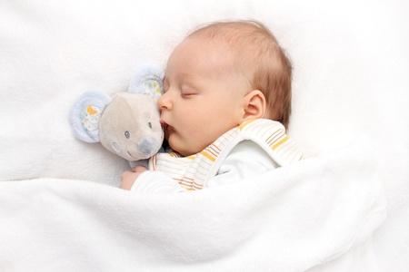 baby toddler asleep in bed with soft toy photo