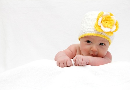 new born baby boy: Baby with a knitted white hat baby on stomach Stock Photo