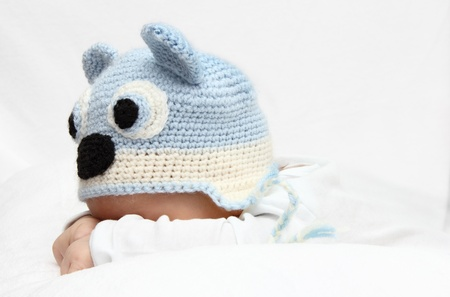 Baby with a knitted blue hat baby on stomach