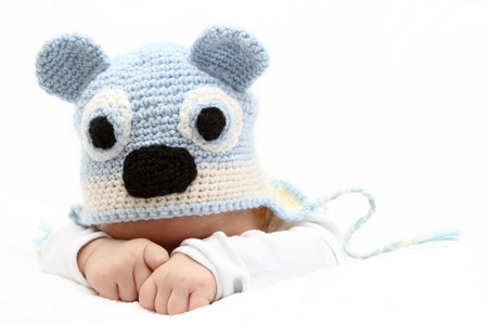 Baby with a knitted blue hat baby on stomach photo