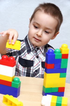 yellow lego block: Child builds a tower with plastic blocks Stock Photo