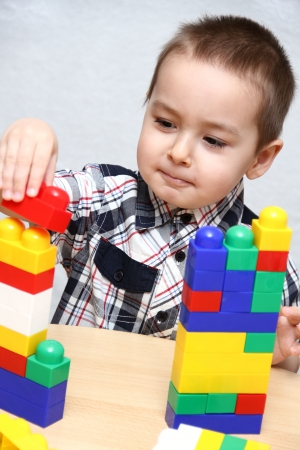 tower block: Child builds a tower with plastic blocks Stock Photo