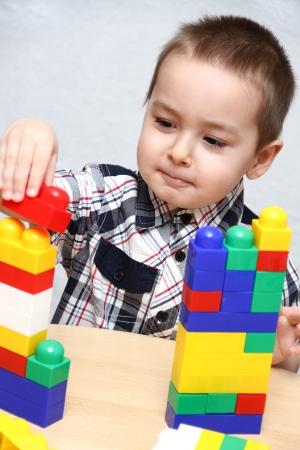 Kind baut einen Turm mit Kunststoff-Blöcke Standard-Bild - 17330117
