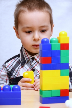Child builds a tower with plastic blocks photo