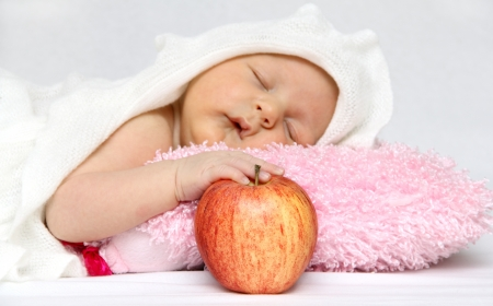 Sleeping baby with an apple in hand photo