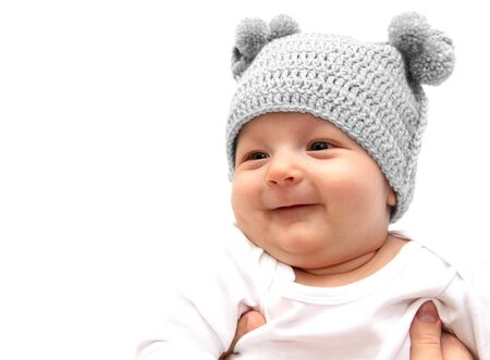 smilling: Happy baby in knitted hat in mothers hands