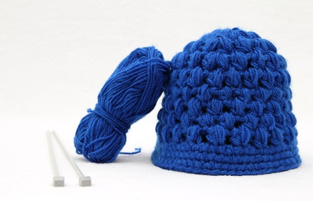 knitten: Knitted blue cap and wool with hook for knitting Stock Photo
