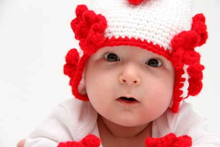 Little baby with knitted white hat with red flowers photo