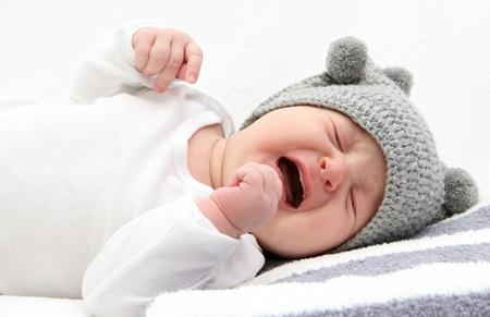 niño llorando: pequeño bebé llorando en la cama Foto de archivo