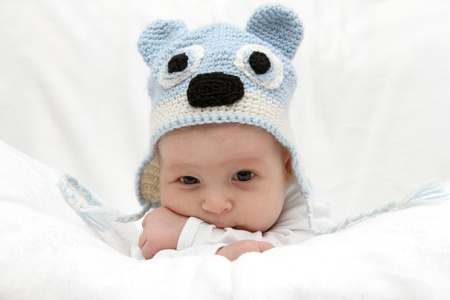 Beautiful baby in  blue hat on the bed