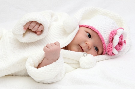 Baby with a knitted white hat photo