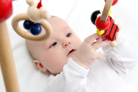 Beautiful baby on back playing with toys photo