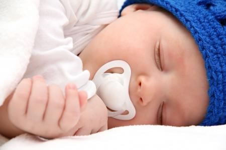 beautiful sleeping newborn baby with pacifier - closeup