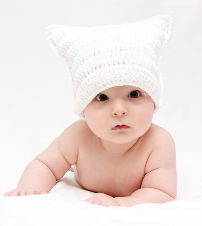 Baby in weißen Hut liegt auf dem Bett Standard-Bild - 18871812