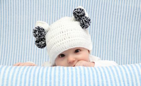 Baby mit einem gestrickten weißen Hut Standard-Bild - 18920455
