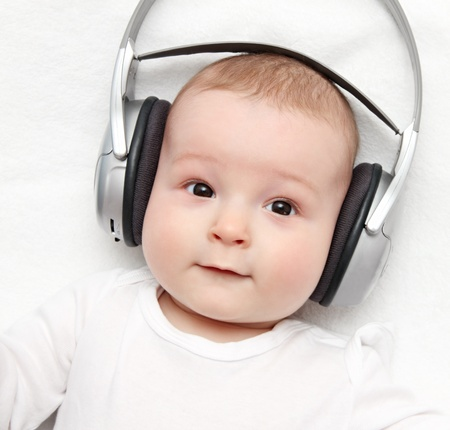 baby with headphone lies on back photo