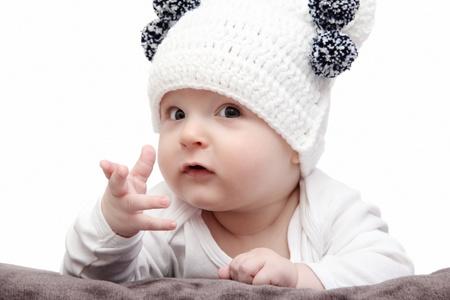 Baby in wei?en Hut liegt auf dem Bett Standard-Bild - 19091472