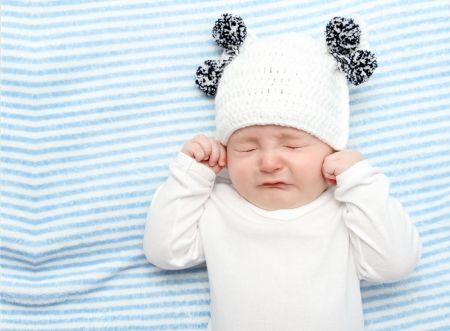 little baby crying on bed Stock Photo