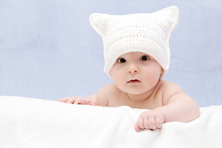 0 6 months: Beautiful baby in white hat lies on bed