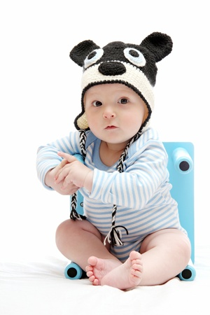 beautiful baby boy with knitted hat sitting  photo