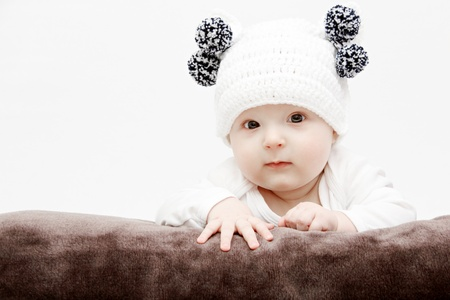 baby in white hat lies on bed