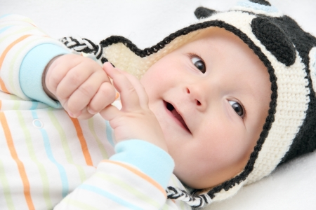 smiling baby lies on back on white bed photo